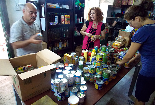 Volunteers talk, unload boxes, sort cans, and stock the shelves