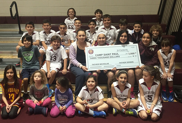 Children of the Archangel Michael Community holding the check to St. Paul Camp