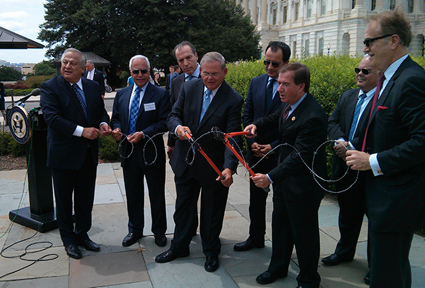 The Chairmen of the Senate Foreign Relations Committee and the House Foreign Affairs Committee, Senator Bob Menendez (D-NJ) and Congressman Ed Royce (R-CA) cut barbed wire to symbolize the desire of the US Congress to end the division and occupation of Cyprus after 40 years. With them (from L to R) are Philip Christopher, Costas Tsentas, Ambassador of Greece to the US Christos Panagopoulos, Ambassador of Cyprus to the US George Chacalli and Andy Manatos, at last year's conference. PHOTO: ETA PRESS