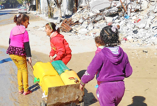 Suha, 10, and Nada, 9, must visit communal water storage tanks daily to fill empty plastic water cans and carry them back to their family homes. Each filled container can weigh up to 44 pounds, a heavy burden for a young child. The need for safe water in Gaza is urgent following extensive damage to water and sewage systems caused by last summer's conflict. IOCC is responding by delivering drinking water to storage tanks in the affected communities. (photo: IOCC)