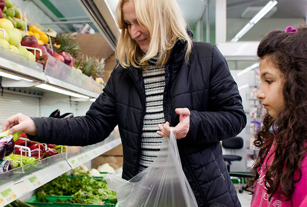 Eleni, 10, and her mother shop for fresh apples and greens at an Athens supermarket using a prepaid grocery card provided by IOCC. (photo: Eirini Vourloumis/IOCC)