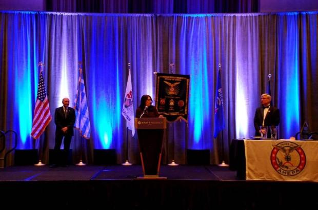 Dr. Laura Calamos Nasir accepting the Aristotle Award on behalf of her father, John Calamos, Sr.