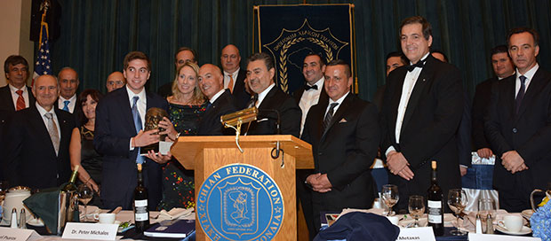 Michael Psaros with his wife Robin and son after receiving the Homeric Award from Chian Federation President John Kontolios. With ther are, Master of Ceremonies John Metaxas, Consul General of the Hellenic Republic Kostas Koutras along with members of the Chian Federation Board.
