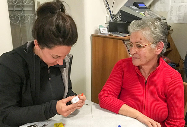 When We Band Together co-founder Zoë Pappis sits with Sophia. Lesvos local Sophia was hired by When We Band Together to sew Zoë Bands.