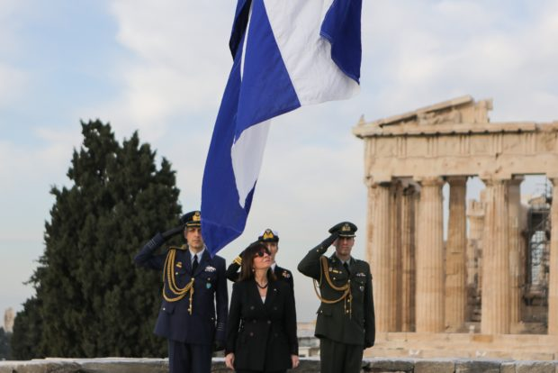 The flag being raised at the Acropolis with President Katerina Sakellaropoulou
